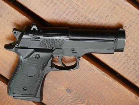 arme de poing noire sur une table en bois près de