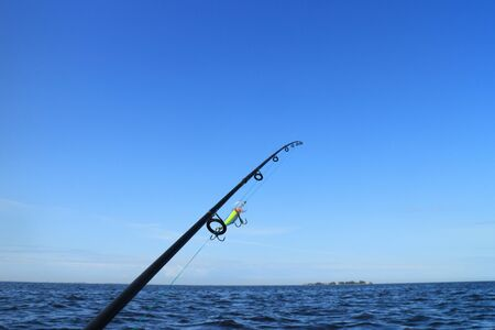 rod with fishing line stretched and crank bait fishing on the sea