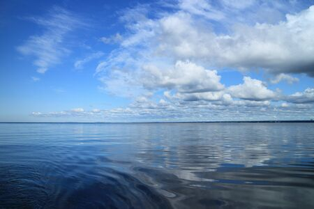 beautiful seascape cumulus clouds reflected in blue water, panorama Stock Photo