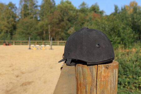 black suede jockey helmet in the foreground on the fence still life