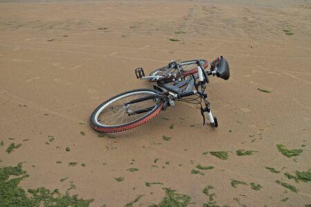 la mountain bike giace sulla sabbia una spiaggia deserta Archivio Fotografico