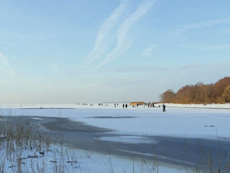 winter  ice fishing  crowd of people on the ice of a frozen and snow-covered lake catching fish