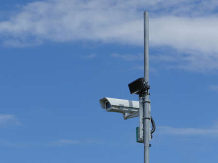 Surveillance camera on a pole high in the blue sky