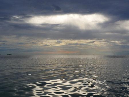 sea dramatic landscape with rays through a cloudy dark sky Standard-Bild