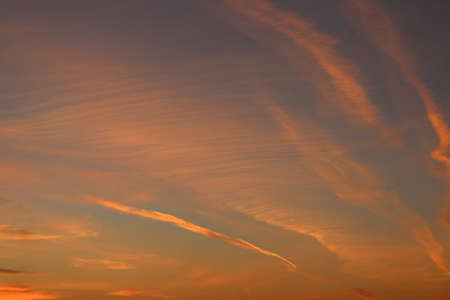 Red aircraft trails in the sky lit by the setting sun
