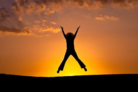 elation: Female silhouette in a jump of elation on a background of a sunset.