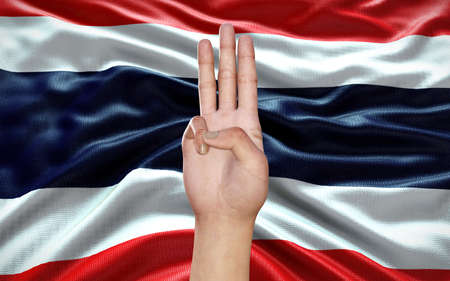 3d Illustration of a hand showing 3 fingers, a political symbol, on Thai flag background, as an act of resistance against Military Government in Thailand. Thailand political situation. Reklamní fotografie - 155965803