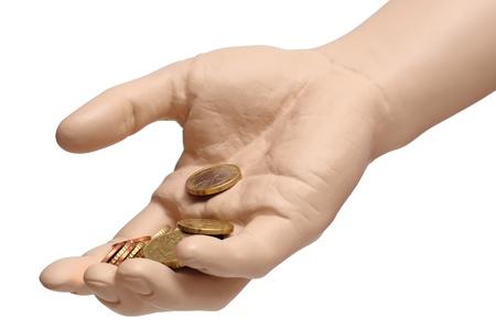 limosna: Una mano de un maniquí que sostiene una pocas monedas de euro aislados en fondo blanco con trazado de recorte