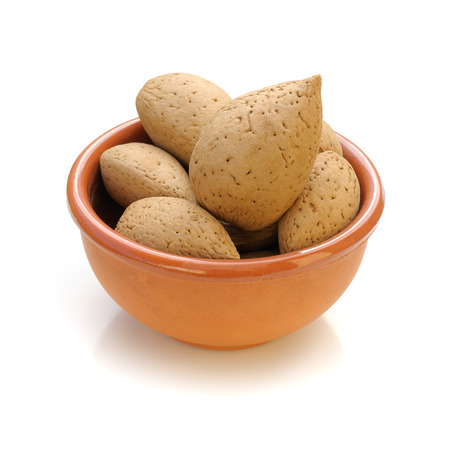 Almonds in a bowl on white background