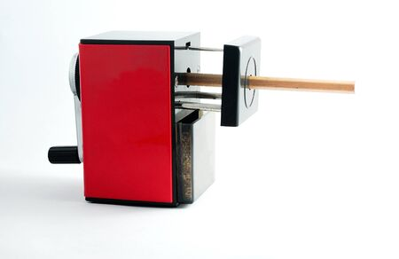 Rotary Pencil Sharpener. Red black rotary pencil sharpener with brown pencil on white background.