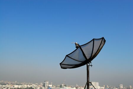 Satellite Dish and Black Aerial Antenna on Rooftop against Blue Sunset Sky and White Cloud on cityscape skyscrapers top view background daylight conceptualized for telecommunication or space network.