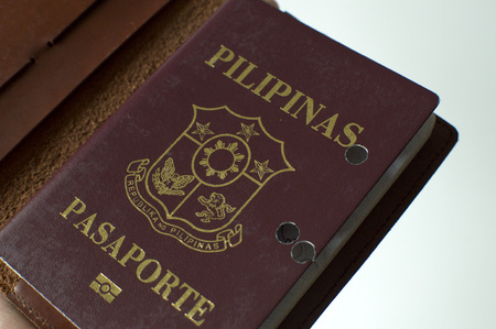 A still life of a old hole-ridden philippine passport against white background Фото со стока
