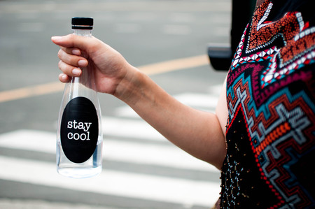 A woman is holding a platic bottle with water outdoor