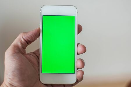 Young man holding a smart phone with green screen