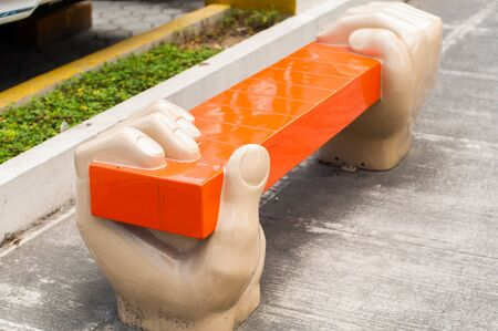 A bench with hands sculpture in the sidewalk Фото со стока
