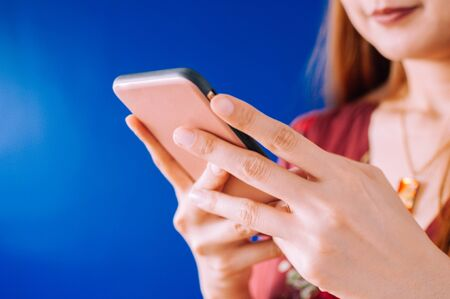 A young woman is using a mobile phone on a blue background