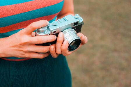 A young woman is carrying a vintage camera outdoor