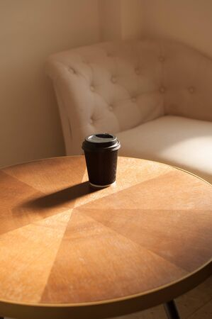 A disposable cup of coffee on a wooden table indoor with sunbeam