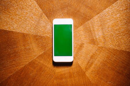 A flat lay of smartphone with green screen on a wooden table Фото со стока