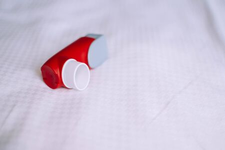 A still life of red and white asthma inhaler devise on a white background Фото со стока