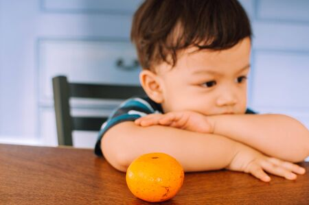 A portrait of a male toddler with orange fruit Stock Photo
