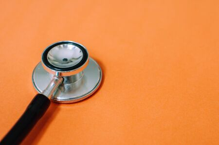 A flat lay still life of stethoscope on an orange background with copy space Фото со стока