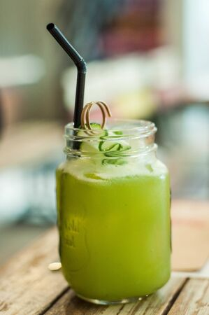 A close-up view of cucumber and lemon juice with plastic straw on a wooden table