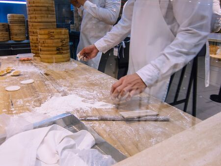 A group of chefs making dumplings in the restaurant