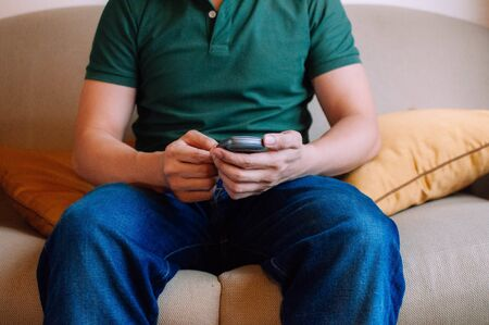 A young male adult is using a device to measure blood sugar while sitting on a couch