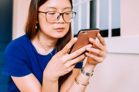 A young Asian woman in casual attire is using a smart phone indoor