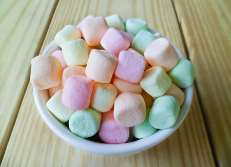 soft colors: marshmallows in white bowl, blur  wood background
