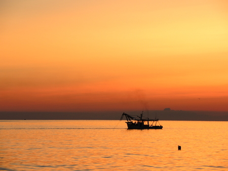 adriatico: Their fishing boats pull nets at the sunrise. Adriatic cost. Emilia Romagna. Italy. Stock Photo
