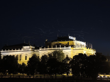 turistic: Night wakes of the gulls lit by the lights over the philharÂmoÂnic opera house in Prague.