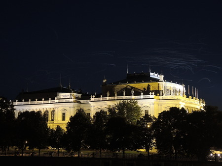 Night wakes of the gulls lit by the lights over the philhar�mo�nic opera house in Prague.
