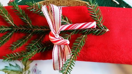 gold table cloth: Christmas ornaments for the table. Red napkin with pine branch.