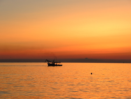 commercial fishing net: Their fishing boats pull nets at the sunrise. Adriatic cost. Emilia Romagna. Italy. Stock Photo