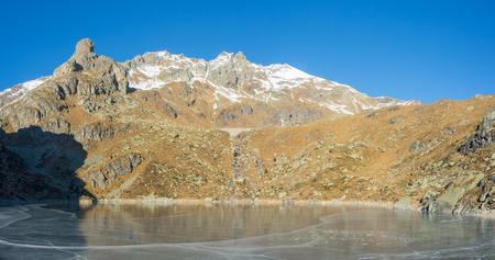 picks: Great landscape at the Orobie Alps in winter. Dry season without snow. Valgoglio, Seriana Valley, Bergamo, Italy. Sucotto artificial lake frozen. Stock Photo