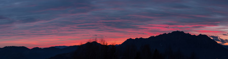 Fiery sunset from mountain pick in a cloudy evening. Fall season. Orobie mountains. Italian Alps.