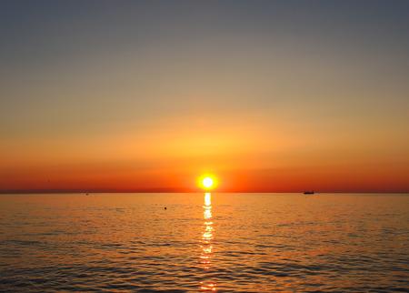 Fiery sunrise at Italian beach. Summer season. Emilia Romagna region. Adriatic sea. Italy