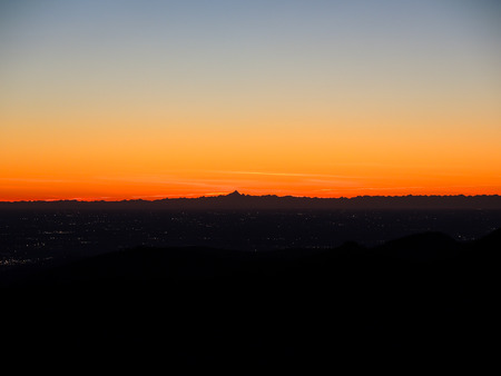 glazes: Fiery sunset from mountain pick with thin glazes in the evening sky. Fall season. Orobie alps. Rena pick. Bergamo Italy. In the distance the Monviso. Stock Photo