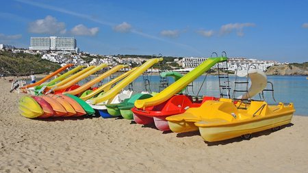 Group of colorful pedal boats with and without slide on the beach of Arenal den Castell, Menorca Island, Spain. Stock Photo