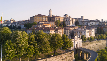 st: Bergamo - Old town. One of the beautiful cities in Italy. Aerial shot of the old gate named Porta San Giacomo during sunrise and a wonderful blue day Stock Photo