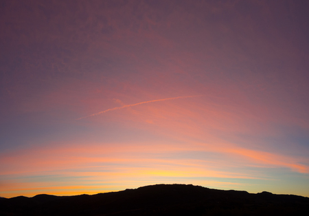 Fiery sunrise from mountain pick with thin glazing in the morning sky