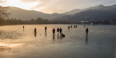 People skating and walking on the frozen lake