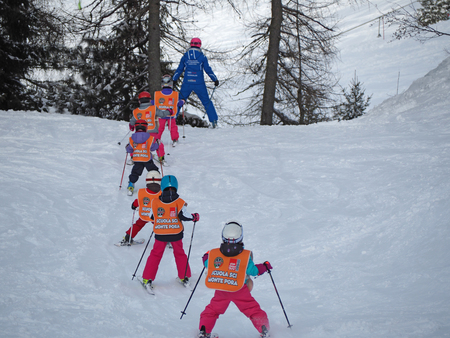 Group of children is learning to ski with the teacher