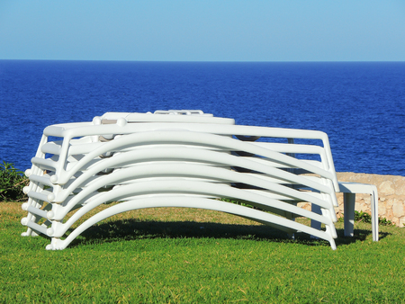 Sun loungers stacked with the background of the sea