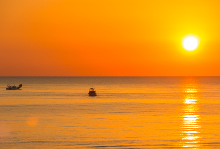 Fishing boats pull their nets at the sunrise.