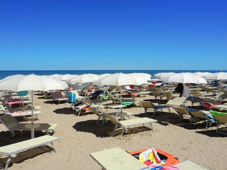 Beach umbrellas, gazebos and sun beds at Italian sandy beaches. Peak season, many people and a lot of mess. Adriatic coast. Emilia Romagna region