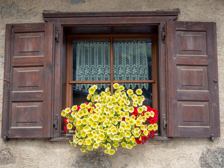 Traditional flowered windows at the Italian Alps and dolomites Archivio Fotografico