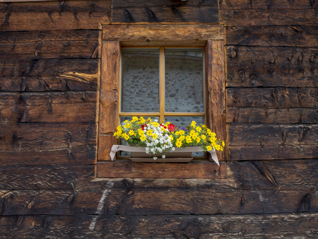 Traditional flowered windows at the Italian Alps and dolomites Stock Photo